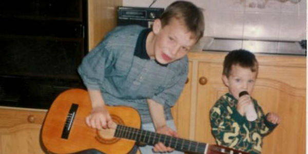 Photo of me aged 10, starting a band with my brother Karl (me on guitar and Karl singing into a bottle)